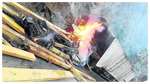 Tráiler cargado de madera se despista, se parte en dos, se incendia y chofer queda grave